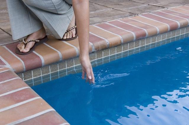 žena se dotýká hladiny bazénu